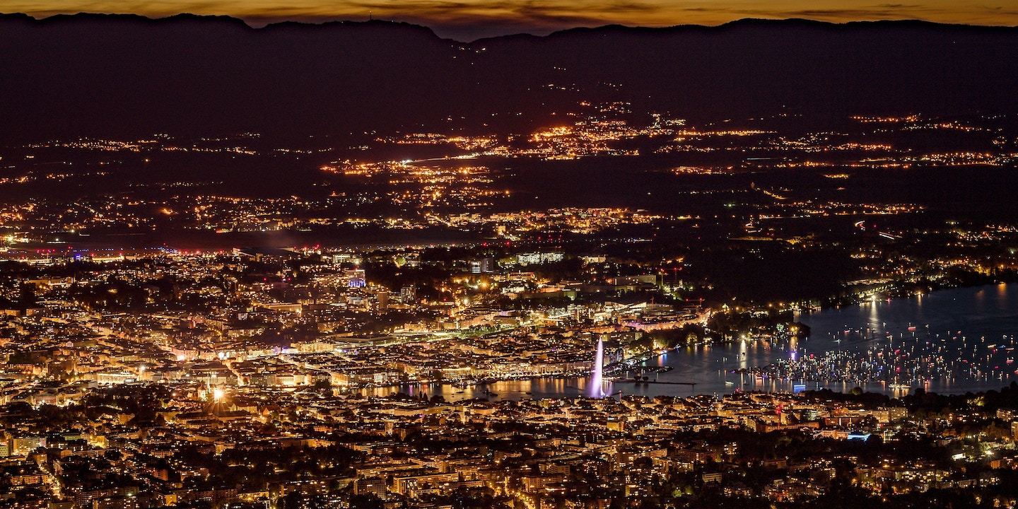 "TOPSHOT - This photograph taken late August 11, 2018, from the French mountain of Saleve shows a nightime view of the city of Geneva at the end of Lake Geneva with its landmark Fountain which is known as ""Jet d'Eau"". (Photo by Fabrice COFFRINI / AFP) (Photo credit should read FABRICE COFFRINI/AFP/Getty Images)"