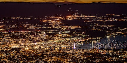 TOPSHOT - This photograph taken late August 11, 2018, from the French mountain of Saleve shows a nightime view of the city of Geneva at the end of Lake Geneva with its landmark Fountain which is known as
