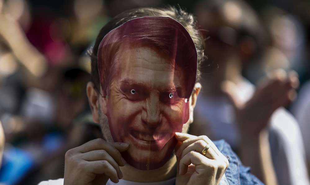 A supporter of Brazilian right-wing presidential candidate Jair Bolsonaro wears a mask of him during a rally at Paulista Avenue in Sao Paulo, Brazil on September 09, 2018. - Supporters of far-right presidential candidate Jair Bolsonaro demonstrated in support of the frontrunner on Sunday, who is convalescing after being stabbed while campaigning several days before. Bolsonaro is hospitalized in the Albert Einstein Hospital in Sao Paulo, which said Sunday that his condition is improving but that he was still receiving nutrients intravenously. (Photo by Miguel SCHINCARIOL / AFP)        (Photo credit should read MIGUEL SCHINCARIOL/AFP/Getty Images)