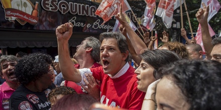 The presidential candidate of Brazil's Workers Party (PT), Fernando Haddad (C), his running mate Manuela D'Avila (R) and Rio's senate candidate Lindbergh Farias (L), take part in a campaign rally at Rocinha Favela in Rio de Janeiro, Brazil, on September 14, 2018. - Brazil holds presidential elections on October 7. (Photo by Mauro Pimentel / AFP)        (Photo credit should read MAURO PIMENTEL/AFP/Getty Images)