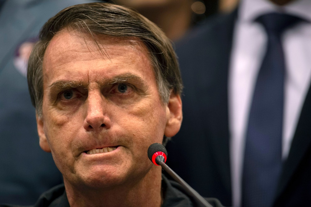 TOPSHOT - Brazil's right-wing presidential candidate for the Social Liberal Party (PSL) Jair Bolsonaro gestures during a press conference in Rio de Janeiro, Brazil on October 11, 2018. - The far-right frontrunner to be Brazil's next president, Jair Bolsonaro, stumbled othe eve by spooking previously supportive investors, while a spate of violent incidents pointed to deep polarization caused by the election race. (Photo by Mauro Pimentel / AFP)        (Photo credit should read MAURO PIMENTEL/AFP/Getty Images)