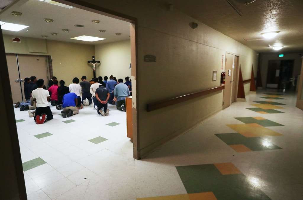 EL PASO, TX - OCTOBER 13:  Migrants pray at an Annunciation House shelter on October 13, 2018 in El Paso, Texas. Annunciation House said it is currently receiving over 700 migrants, all families, released from ICE holding cells per week. Most migrants say they are fleeing desperate conditions in their home countries. (Photo by Mario Tama/Getty Images)