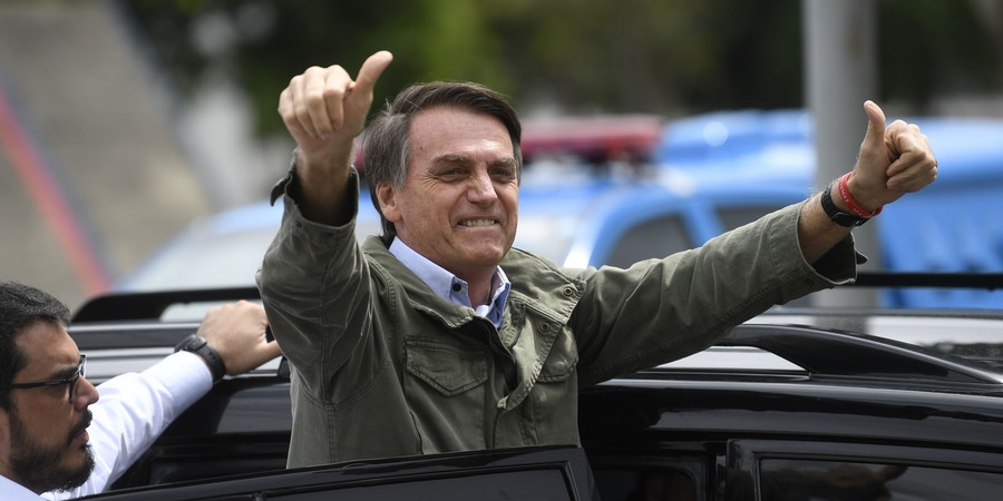 Jair Bolsonaro, far-right lawmaker and presidential candidate for the Social Liberal Party (PSL), gives thumbs up to supporters, during the second round of the presidential elections, in Rio de Janeiro, Brazil on October 28, 2018. - Brazilians will choose their president today during the second round of the national elections between the far-right firebrand Jair Bolsonaro and leftist Fernando Haddad (Photo by MAURO PIMENTEL / AFP)        (Photo credit should read MAURO PIMENTEL/AFP/Getty Images)