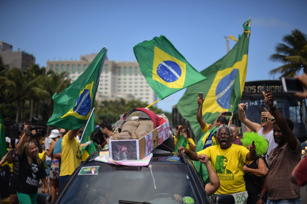 Supporters of far-right lawmaker and presidential candidate for the Social Liberal Party (PSL), Jair Bolsonaro, parade a fake coffin representing the Worker's Party (PT), in Rio de Janeiro, Brazil, during the second round of the presidential elections, on October 28, 2018. - Brazilians will choose their president today during the second round of the national elections between the far-right firebrand Jair Bolsonaro and leftist Fernando Haddad (Photo by Carl DE SOUZA / AFP)        (Photo credit should read CARL DE SOUZA/AFP/Getty Images)