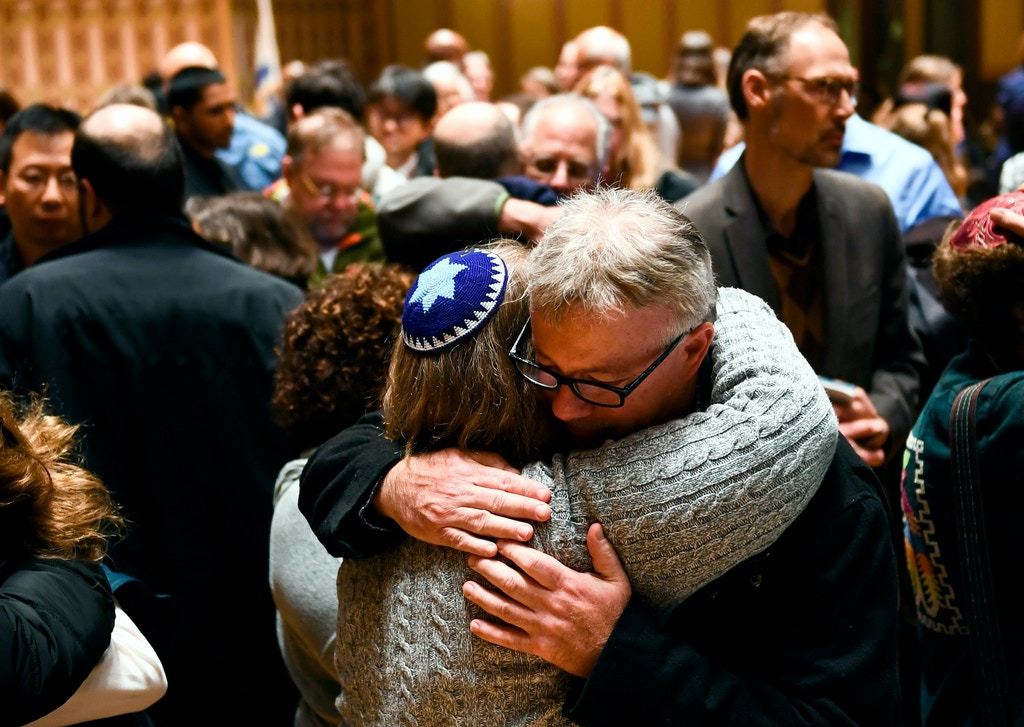 "People hug after a vigil, to remember the victims of the shooting at the Tree of Life synagogue the day before, at the Allegheny County Soldiers Memorial on October 28, 2018, in Pittsburgh, Pennsylvania. - A man suspected of bursting into a Pittsburgh synagogue during a baby-naming ceremony and gunning down 11 people has been charged with murder, in the deadliest anti-Semitic attack in recent US history. The suspect -- identified as a 46-year-old Robert Bowers -- reportedly yelled ""All Jews must die"" as he sprayed bullets into the Tree of Life synagogue during Sabbath services on Saturday before exchanging fire with police, in an attack that also wounded six people. (Photo by Brendan Smialowski / AFP)        (Photo credit should read BRENDAN SMIALOWSKI/AFP/Getty Images)"