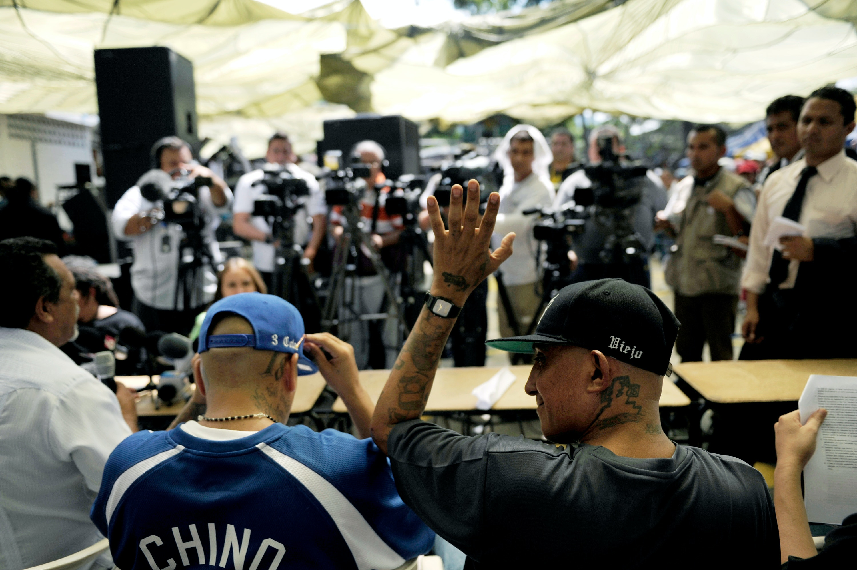 "The leader of the Mara 18 (18th Street Gang), Carlos Mojica Lechuga, a.k.a. ""El Viejo Lin"" (R), gestures during a press conference at the Female Jail in San Salvador, El Salvador on September 24, 2012. The leaders of the Mara 18 and Salvatrucha offered a press conference during the celebration of the 200 days of truce between them to reduce murder.  AFP PHOTO/Jose CABEZAS        (Photo credit should read Jose CABEZAS/AFP/GettyImages)"