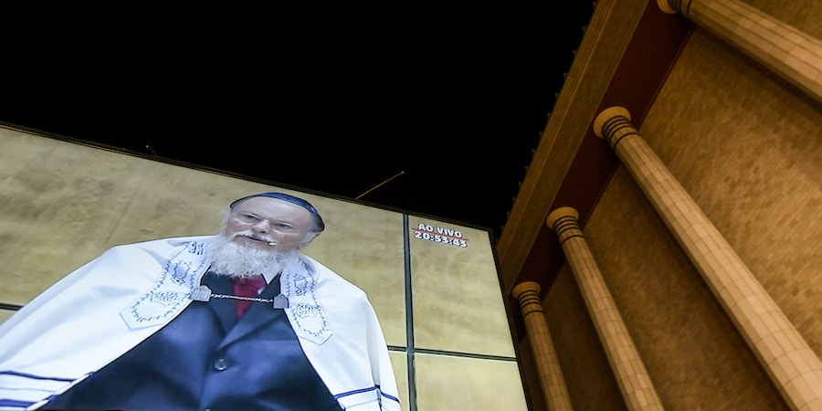 Billionaire Edir Macedo, owner and chairman of Rede Record de Televisao Angola Lda, is projected on a screen displayed outside a replica of Solomon's Temple during its inauguration ceremony in Sao Paulo, Brazil, on Thursday, July 31, 2014. Billionaire Edir Macedo's temple spans two city blocks and cost 680 million reais ($300 million) to erect. Macedo's net worth has grown to $1.5 billion since he bought the Record TV network in 1989 with a $45 million interest-free loan from the Universal Church of the Kingdom of God, which he founded, according to the Bloomberg Billionaires Index. Photographer: Paulo Fridman/Bloomberg via Getty Images
