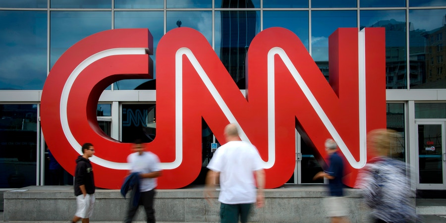 Pedestrians pass in front of CNN signage displayed at the network's headquarters building in Atlanta, Georgia, U.S., on Friday, Aug. 1, 2014. Time Warner is a