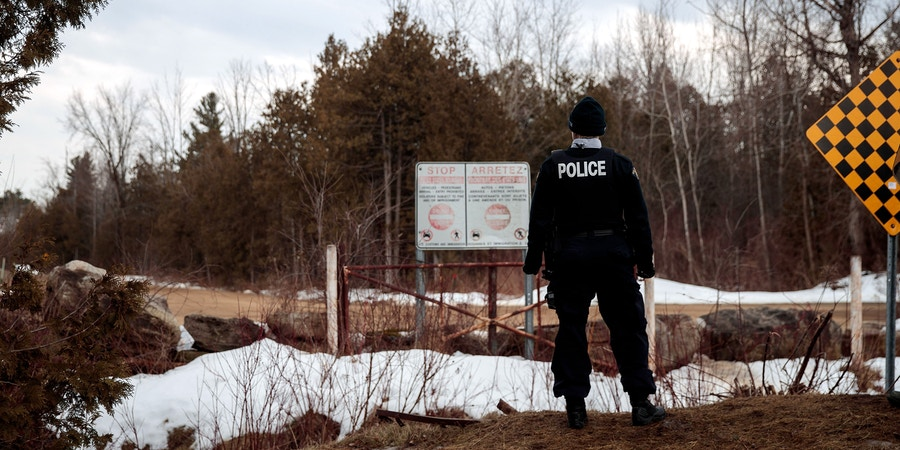 HEMMINGFORD, QUEBEC - FEBRUARY 23: A Royal Canadian Mounted Police officer stands at the U.S.-Canada, February 23, 2017 in Hemmingford, Quebec, Canada. In the past month, hundreds of people have crossed Quebec land border crossings in attempts to seek asylum and claim refugee status in Canada. (Photo by Drew Angerer/Getty Images)