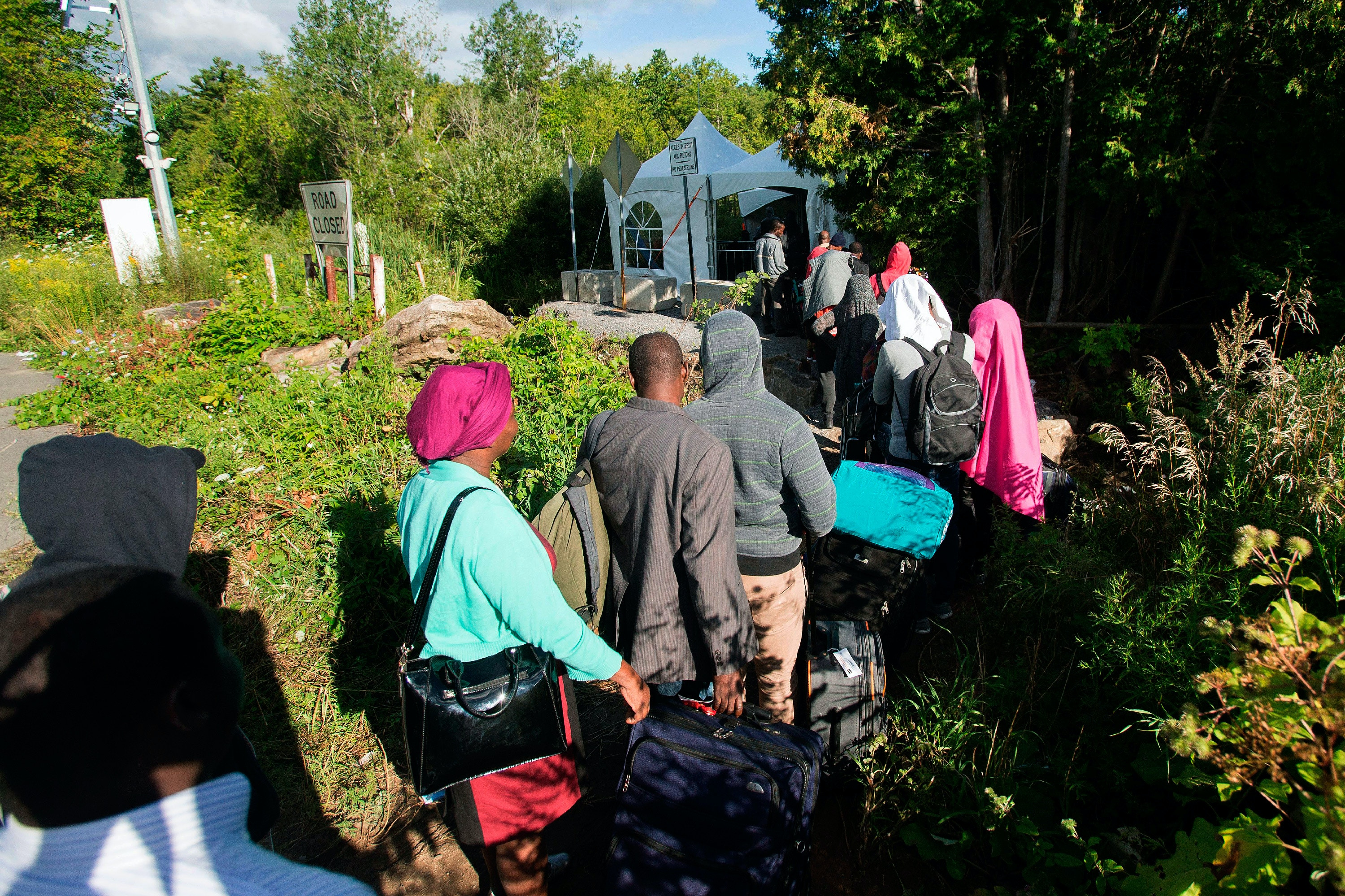TOPSHOT - A long line of asylum seekers wait to illegally cross the Canada/US border near Champlain, New York on August 6, 2017. - In recent days the number of people illegally crossing the border has grown into the hundreds. (Photo by Geoff Robins / AFP)(Photo credit should read GEOFF ROBINS/AFP/Getty Images)