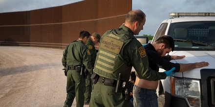 Border Patrol agents apprehend illegal immigrants shortly after they crossed the border from Mexico into the United States on Monday, March 26, 2018 in the Rio Grande Valley Sector near McAllen, Texas.An estimated 11 million undocumented immigrants live in the United States, many of them Mexicans or from other Latin American countries. / AFP PHOTO / Loren ELLIOTT (Photo credit should read LOREN ELLIOTT/AFP/Getty Images)