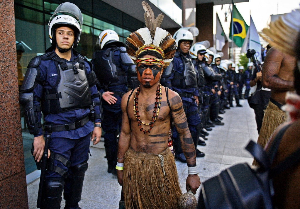 A Brazilian indigenous man walks past riot police during a protest against the government's decision not to  recognize the land demarcation of indigenous people living in Raposa Serra do Sol, Roraima State, in Brasilia, on April 25, 2018. - About 2,500 indigenous people from different tribes are taking part in the Indigenous National Mobilization (MNI) week - a mobilization which seeks to tackle territorial rights' negotiations with the government. (Photo by CARL DE SOUZA / AFP)        (Photo credit should read CARL DE SOUZA/AFP/Getty Images)