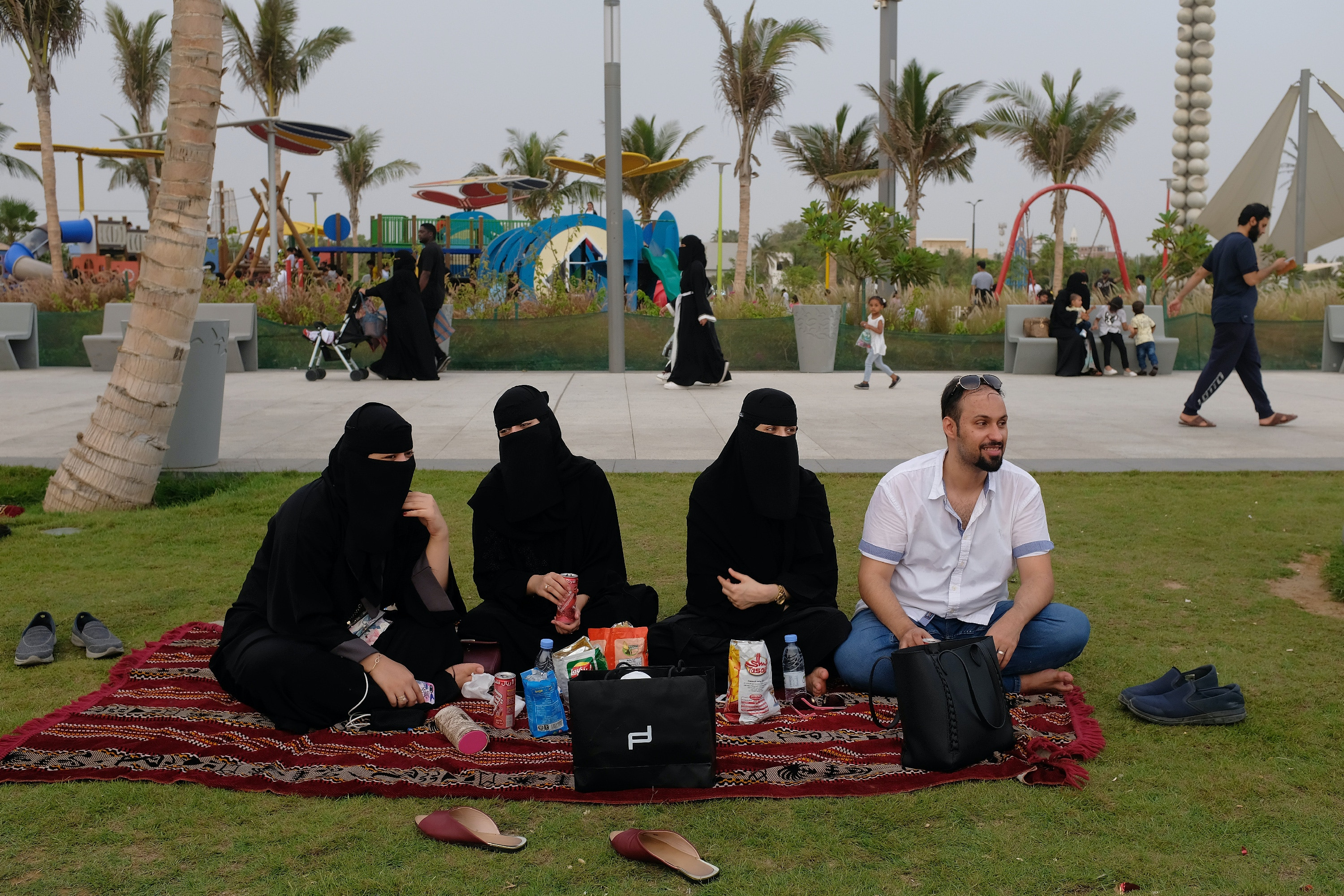 JEDDAH, SAUDI ARABIA - JUNE 22:  Young Saudis, including three women wearing the traditional niqab and black abayas, relax on the Corniche waterfront on June 22, 2018 in Jeddah, Saudi Arabia. The Saudi government, under Crown Prince Mohammad Bin Salman, is phasing in an ongoing series of reforms to both diversify the Saudi economy and to liberalize its society. The reforms also seek to empower women by restoring them basic legal rights, allowing them increasing independence and encouraging their participation in the workforce. Saudi Arabia is among the most conservative countries in the world and women have traditionally had much fewer rights than men.  (Photo by Sean Gallup/Getty Images)