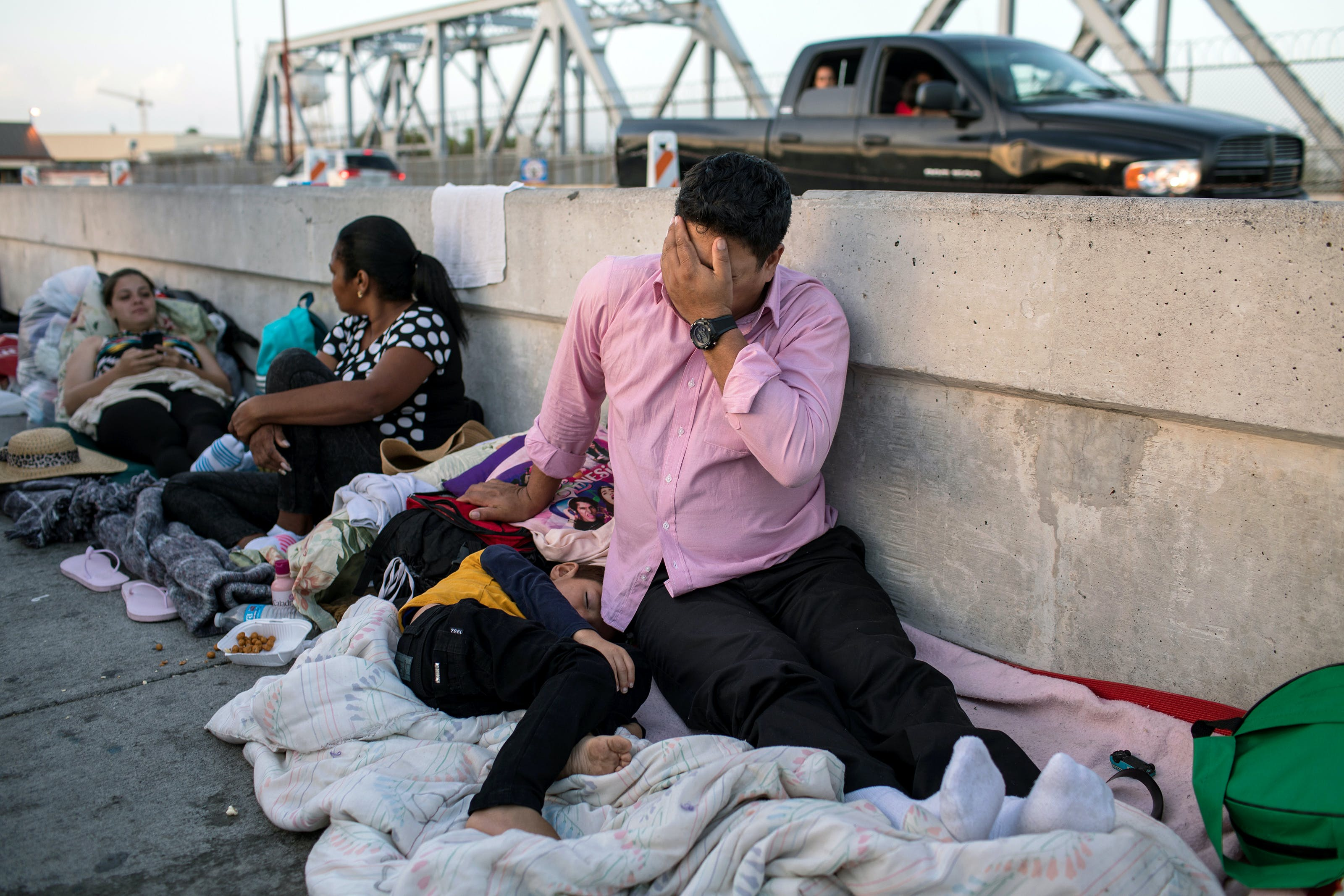 MATAMOROS, MX - JUNE 28: A Honduran man and his 5-year-old son wait on the Mexican side of the Brownsville
