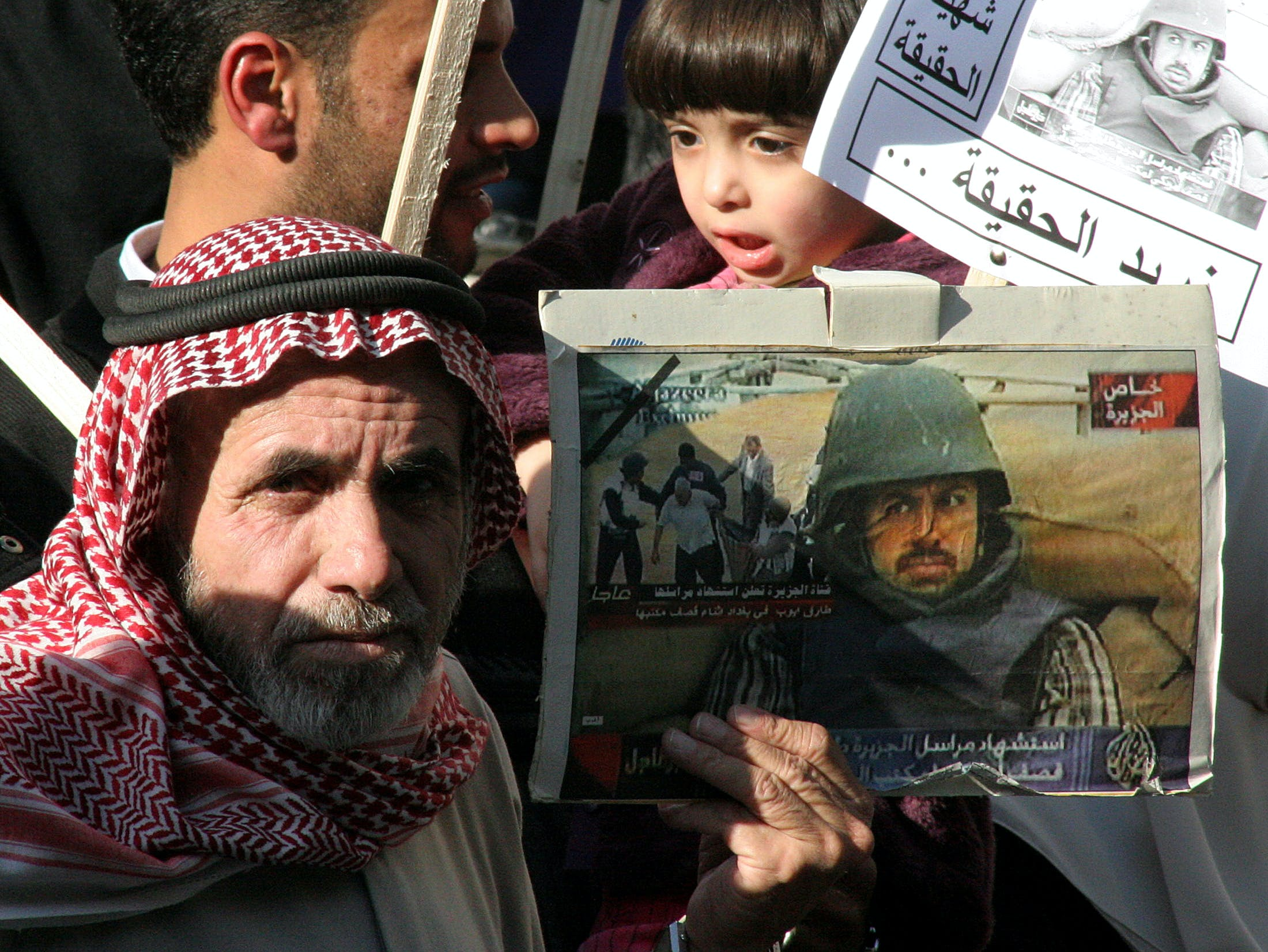Fatima Ayyoub (top R), 4, daughter of Jordanian Al Jazeera correspondent Tareq Ayyoub, is seen next to pictures of her father with Naeem Ayoub (L), father of Tareq Ayyoub, during a protest outside the Al Jazeera office in Amman Novmber 24, 2005. Ayyoub was a victim of a missile attack that hit the Al Jazeera bureau in Baghdad on April 8, 2003. Britain has warned media organisations they are breaking the law if they publish details of a leaked document said to show U.S. President George W. Bush wanted to bomb Arabic television station Al Jazeera. REUTERS/Majed Jaber - RP2DSFHMGFAD
