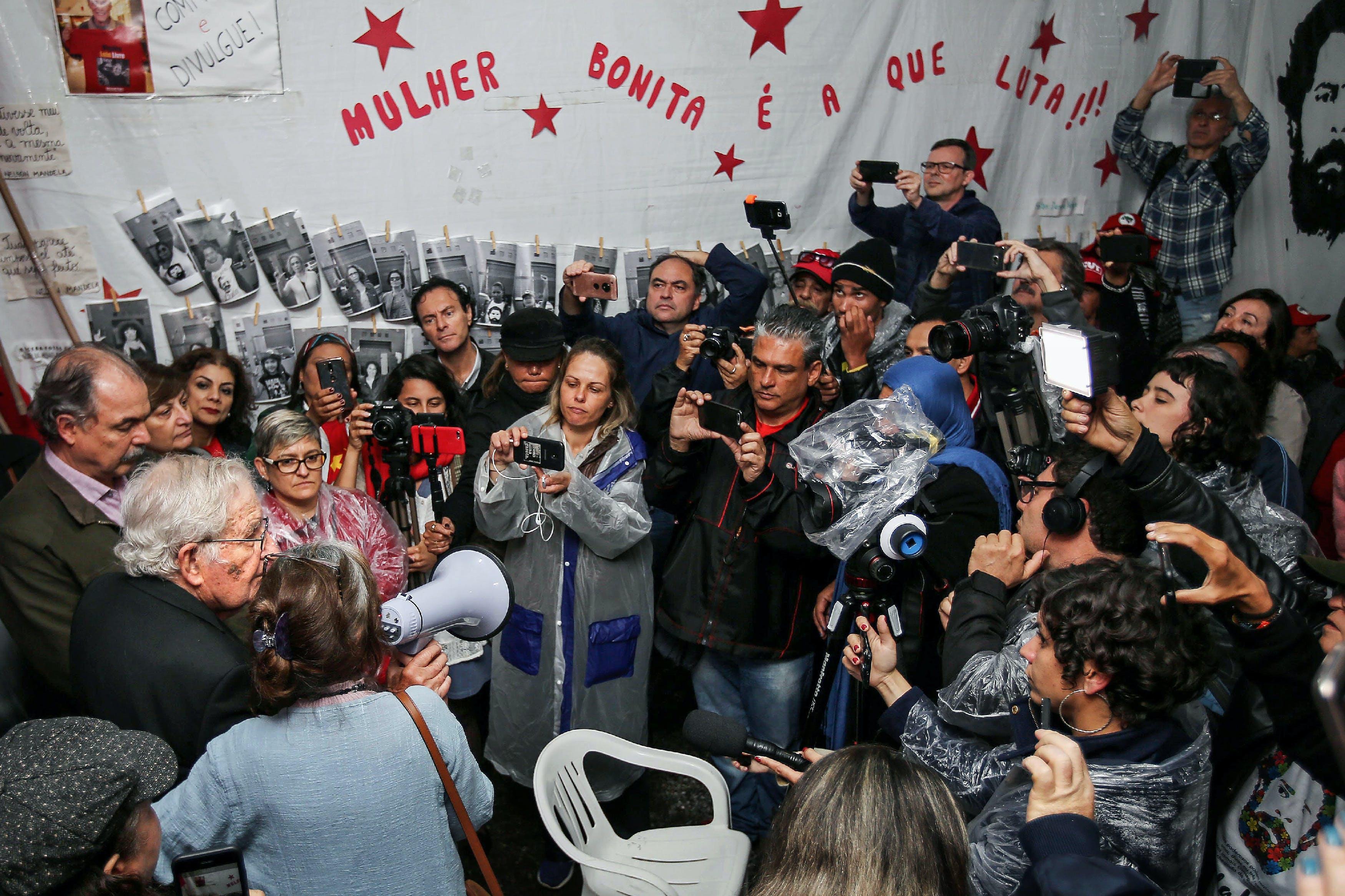 Linguista americano e ativista político, Noam Chomsky (à esquerda) fala com militantes do PT depois de visitar o presidente Luiz Inácio Lula da Silva na prisão no dia 20 setembro.