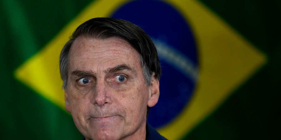 Brazil's right-wing presidential candidate for the Social Liberal Party (PSL) Jair Bolsonaro gestures in front of the Brazilian flag as he prepares to cast his vote during the general elections, in Rio de Janeiro, Brazil, on October 7, 2018. - Polling stations opened in Brazil on Sunday for the most divisive presidential election in the country in years, with far-right lawmaker Jair Bolsonaro the clear favorite in the first round. About 147 million voters are eligible to cast ballots and choose who will rule the world's eighth biggest economy. New federal and state legislatures will also be elected. (Photo by Mauro PIMENTEL / AFP)        (Photo credit should read MAURO PIMENTEL/AFP/Getty Images)