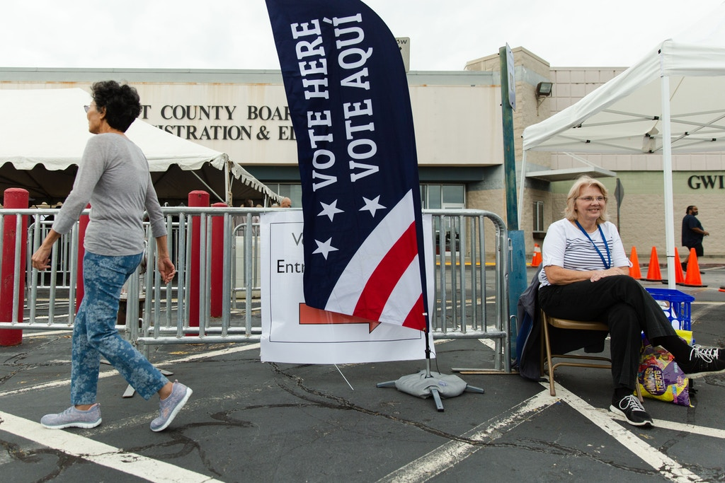 Shirley Barnard, right, a poll worker at the Gwinnett County (Ga.) Voter Registrations and Elections Office in Lawrenceville, Ga.  sits at the entrance for voters on Wednesday, Oct. 17, 2018. Photo by Kevin D. Liles for The Intercept