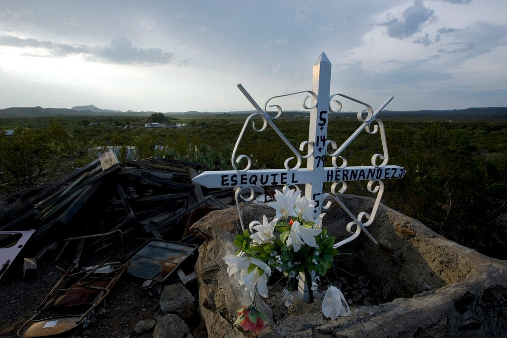 A cross honoring  Esequiel Hernandez, Jr. sits on the place he fell dead in Redford, Texas, Saturday, July 26, 2008. Redford, a knot of adobe homes and alfalfa fields some 300 miles down river from El Paso, made headlines in 1997 when U.S. Marines on a secret anti-drug mission mistakenly gunned down a local high school student, Esequiel Hernandez, Jr., as he herded goats along the Rio Grande. Residents on both sides of the Big Bend, as the curve is known, are relieved their unspoiled desert boundary has been largely left out of plans to wall off 700 miles of the United States' southern border _ even if the unfenced frontier may draw more smugglers and migrants as the rest of the line is sealed off. (AP Photo/Guillermo Arias)