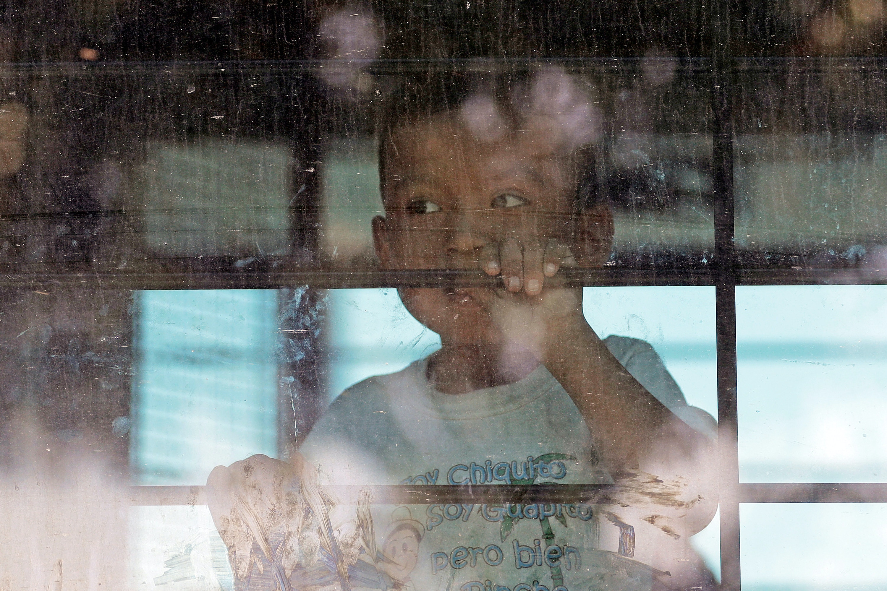 An immigrant child looks out from a U.S. Border Patrol bus leaving as protesters block the street outside the U.S. Border Patrol Central Processing Center Saturday, June 23, 2018, in McAllen, Texas. Additional law enforcement officials were called in to help control the crowd and allow the bus to move. (AP Photo/David J. Phillip)