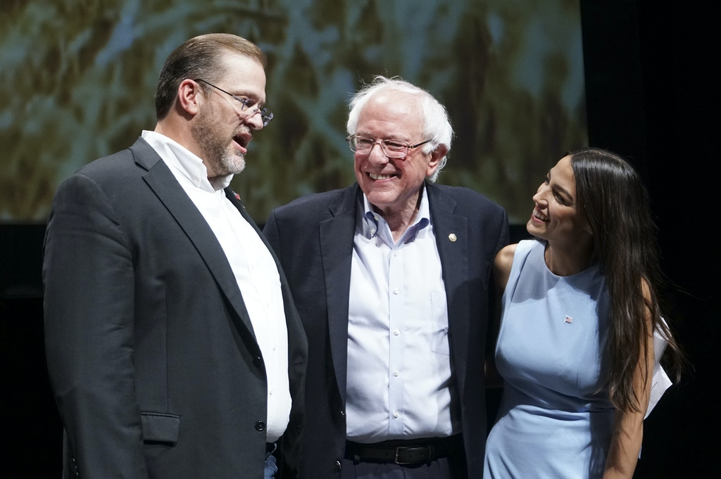 FILE - In this July 20, 2018, file photo, Democratic Kansas U.S. congressional candidate James Thompson, left, U.S. Sen. Bernie Sanders, I-Vt., and Alexandria Ocasio-Cortez, a Democratic congressional candidate from New York, stand together on stage after a rally in Wichita, Kan. Thompson cruised to victory in the Democratic primary after getting visits from Ocasio-Cortez and Sen. Bernie Sanders on the campaign trail. (Jaime Green/The Wichita Eagle via AP, File)