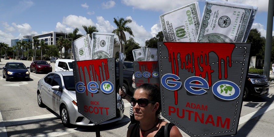 Alessandra Mondolfi takes part in the Dream Defenders protest against the Geo Group's temporary headquarters in Boca Raton, Fla., on Tuesday, Aug. 7, 2018. (Carline Jean /South Florida Sun-Sentinel via AP)