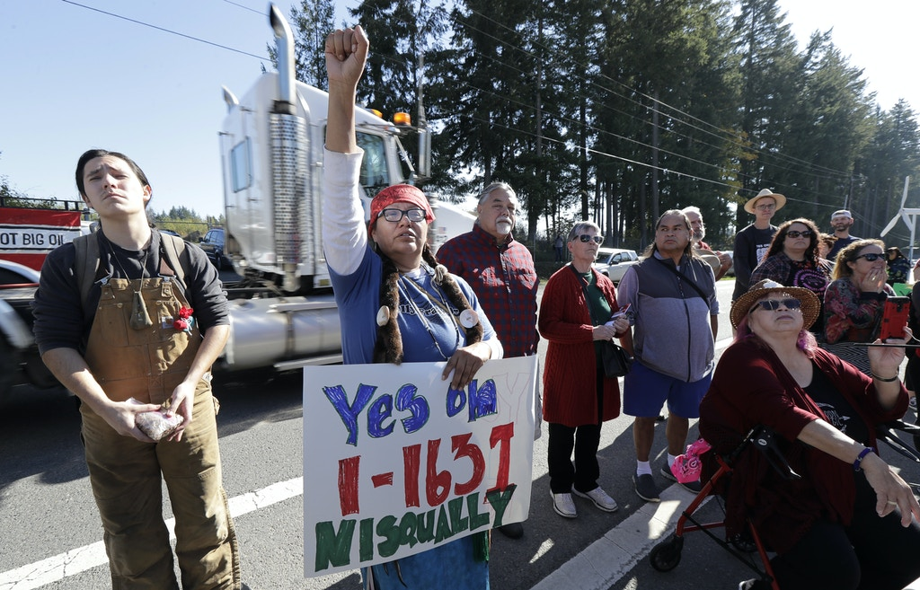 A supporter of Initiative 1631 holds a sign referencing the Nisqually Indian Tribe, Wednesday, Oct. 17, 2018, during a rally supporting I-1631, a November ballot measure in Washington state that would charge a fee on carbon emissions from fossil fuels. The rally was organized by tribal and environmental leaders, and took place near the offices of the Western States Petroleum Association in Lacey, Wash. (AP Photo/Ted S. Warren)