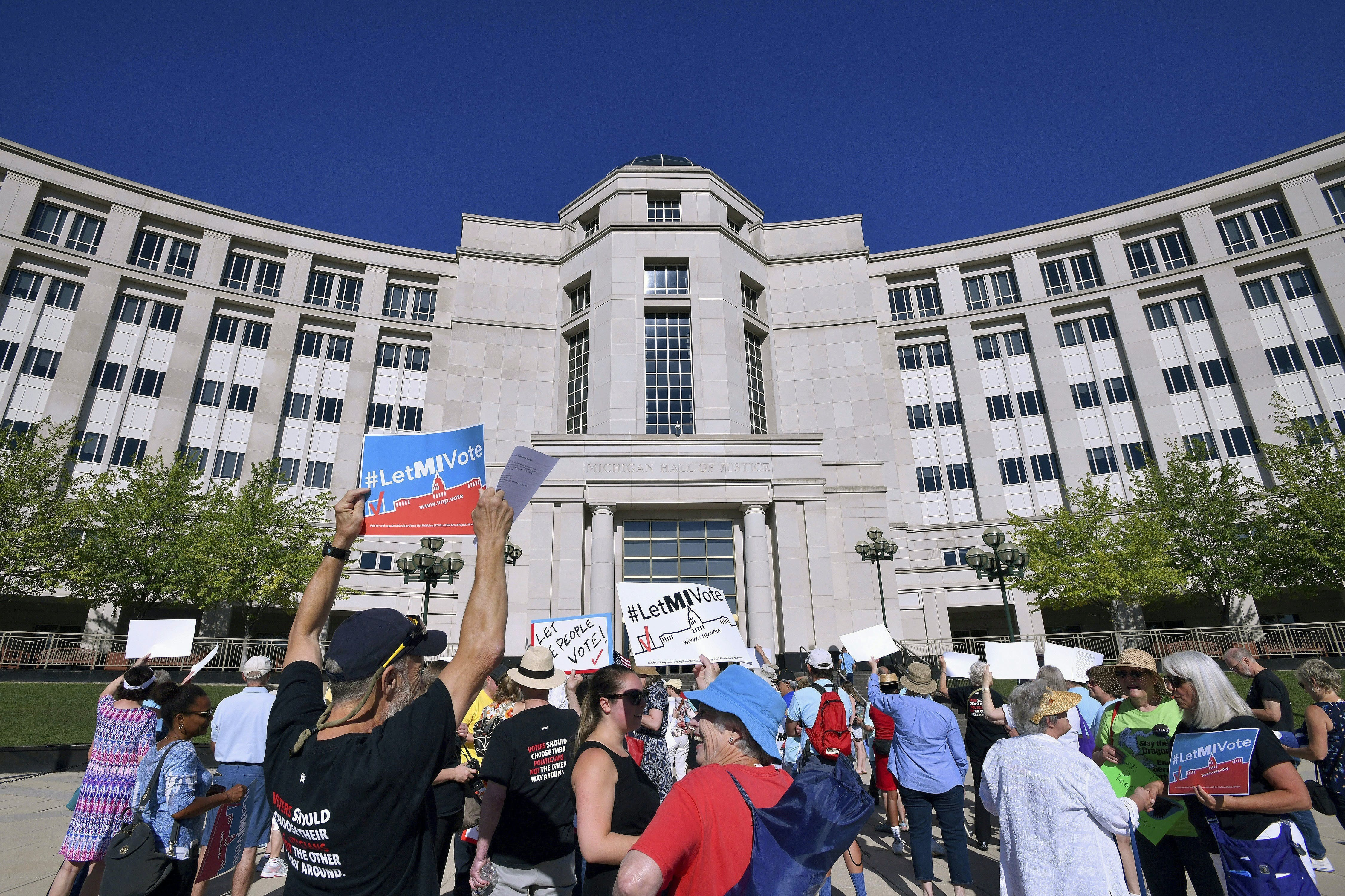 "FILE- In this July 18, 2018, file photo, demonstrators rally outside the Michigan Hall of Justice in Lansing, Mich., where the state's Supreme Court heard arguments about whether voters in November should be able to pass a constitutional amendment that would change how the state's voting maps are drawn. A growing movement to curb partisan gerrymandering is being put to the test in the Nov. 6 elections with several state ballot measures intended to make congressional and state legislative districts more ""fair."" (Dale G. Young/The Detroit News via AP, File)"