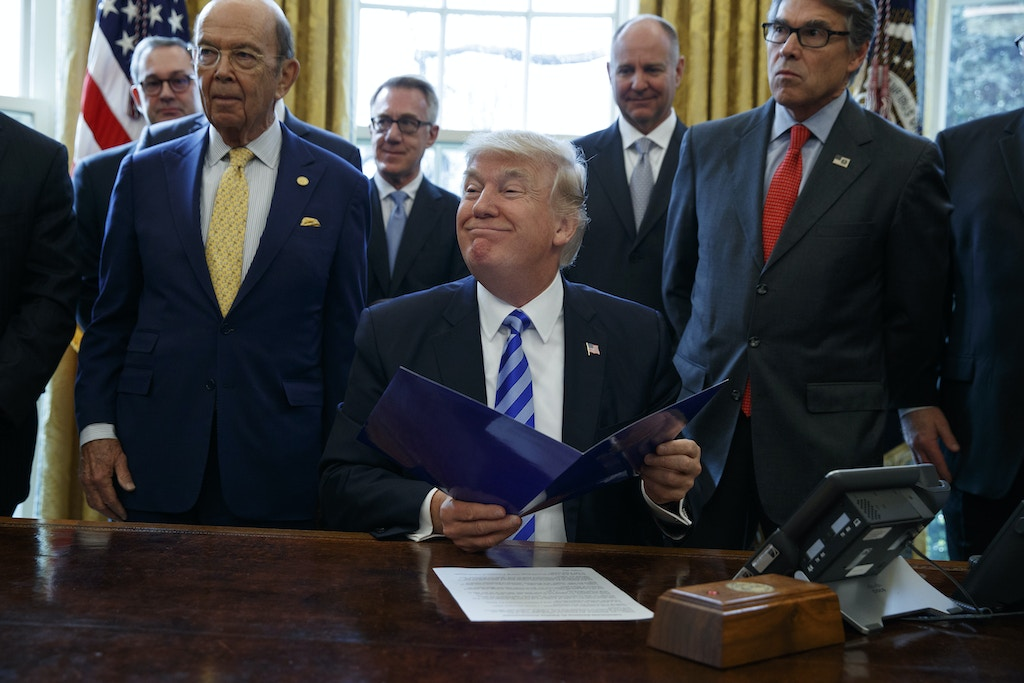 FILE - In this March 24, 2017 file photo, President Donald Trump, flanked by Commerce Secretary Wilbur Ross, left, and Energy Secretary Rick Perry, is seen in the Oval Office of the White House in Washington, during the announcing of the approval of a permit to build the Keystone XL pipeline, clearing the way for the $8 billion project.A federal judge in Montana has blocked construction of the $8 billion Keystone XL Pipeline to allow more time to study the project's potential environmental impact. U.S. District Judge Brian Morris' order on Thursday, Nov. 8, 2018,  came as Calgary-based TransCanada was preparing to build the first stages of the oil pipeline in northern Montana. Environmental groups had sued TransCanada and The U.S. Department of State in federal court in Great Falls.  (AP Photo/Evan Vucci, File)