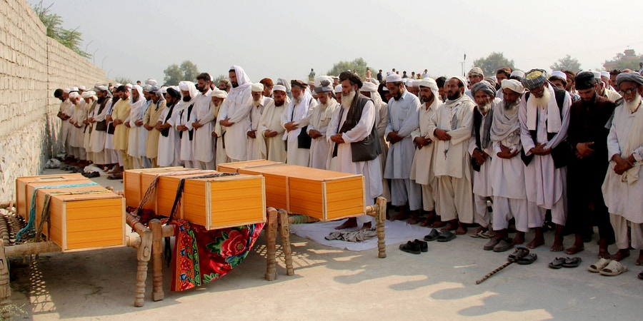 Afghan men offer funeral prayers near the bodies of civilians killed in a NATO air strike, on the outskirts of Jalalabad, east of Kabul, Afghanistan, Saturday, Oct. 5, 2013. An Afghan official says a NATO strike in the country's east has killed several civilians, but the U.S.-led coalition says that it targeted insurgents and that its initial reports indicate no civilian casualties. Afghan and NATO officials regularly differ as to whether civilians have been hit in attacks. Afghan President Hamid Karzai has made denunciations of reported civilian deaths in airstrikes a pillar of his political strategy. (AP Photo/Nisar Ahmad)