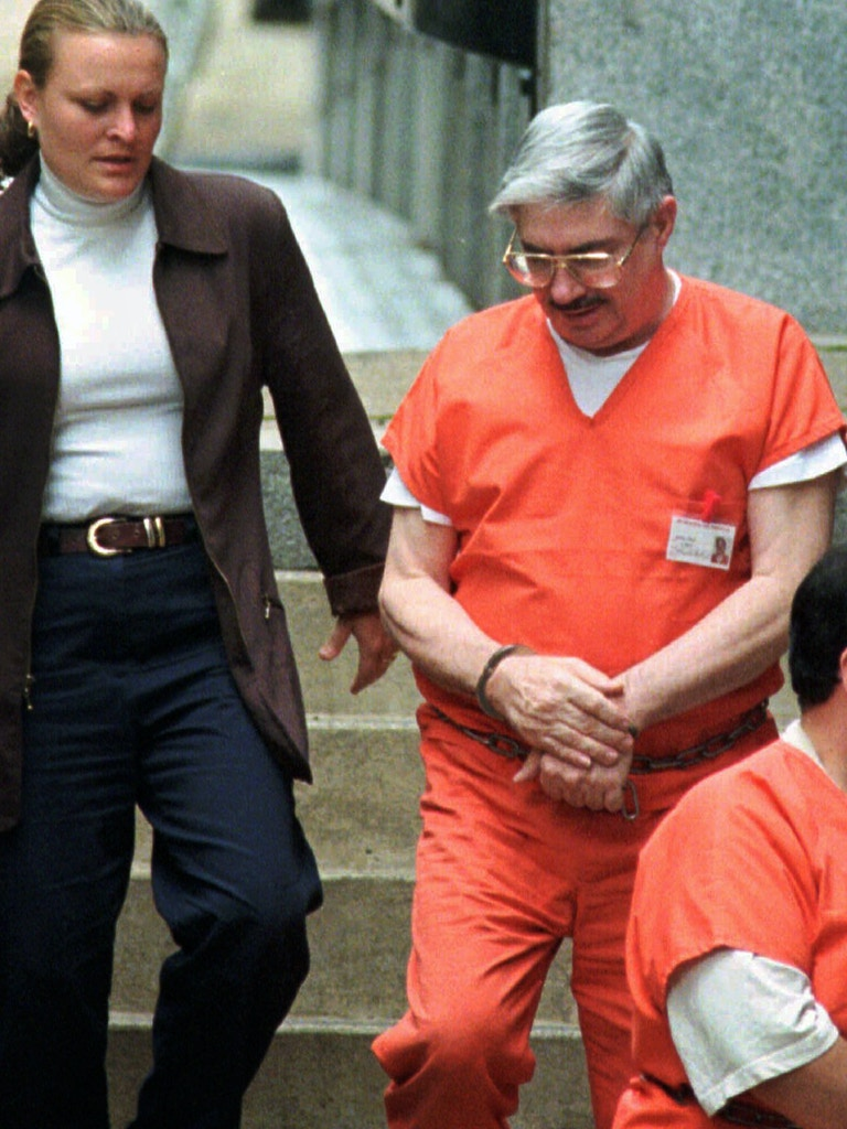 A law enforcement officer escorts Floyd Ray Looker, self-proclaimed head of the Mountaineer Militia, into the federal courthouse in Wheeling, W. Va., for his second trial Wednesday, Aug. 13, 1997. Looker pleaded guilty Wednesday to selling copies of blueprints of the FBI's fingerprint complex to what he believed was a terrorist group that planned to blow the center up. Looker actually sold the copies for $50,000 to an undercover FBI agent posing as a middleman for the terrorists. (AP Photo/Gary Tramontina)