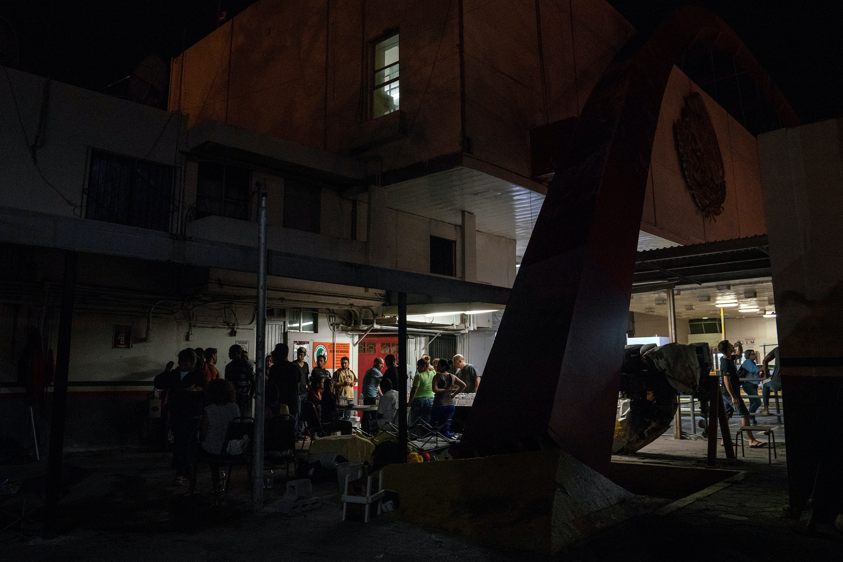 Asylum seekers gather to eat the food brought to them by volunteers near the Gateway International Bridge in Matamoros, Tamaulipas on Nov. 5, 2018. Photo: Verónica G. Cárdenas for The Intercept