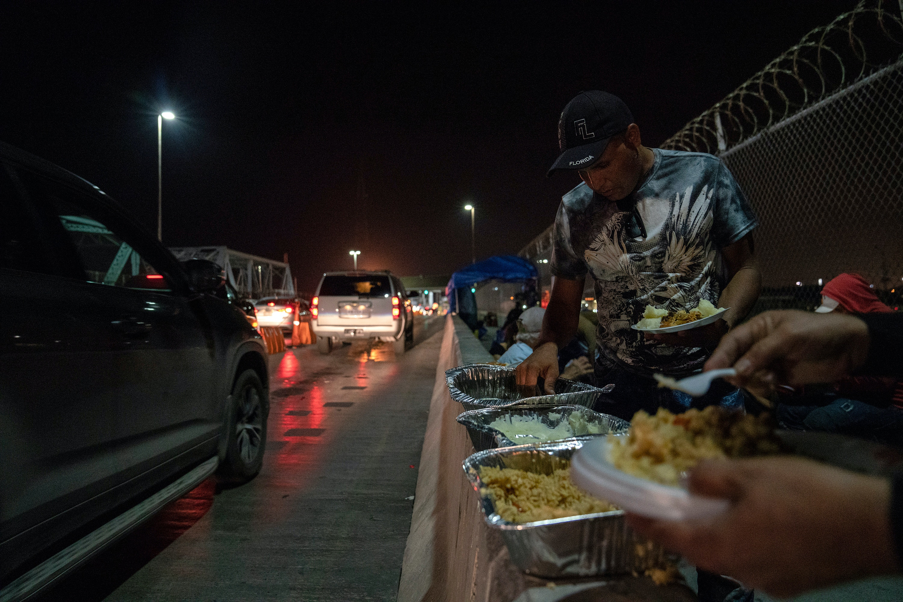 Asylum seekers gather to eat the food brought to them by volunteers at the Brownsville-Matamoros International Bridge in Matamoros, Tamaulipas on Nov. 5, 2018.  Photo: Verónica G. Cárdenas for The Intercept