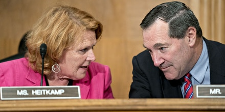 Senator Joe Donnelly, a Democrat from Indiana, right, talks to Senator Heidi Heitkamp, a Democrat from North Dakota, during a Senate Banking Committee hearing in Washington, D.C., U.S., on Tuesday, Aug. 21, 2018. The hearing was titled Russia Sanctions: Current Effectiveness and Potential for Next Steps. Photographer: Andrew Harrer/Bloomberg via Getty Images