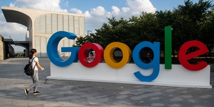 A woman and her child play on a Google sign at the World Artificial Intelligence Conference (WAIC) in Shanghai on September 26, 2018. (Photo by Johannes EISELE / AFP)        (Photo credit should read JOHANNES EISELE/AFP/Getty Images)