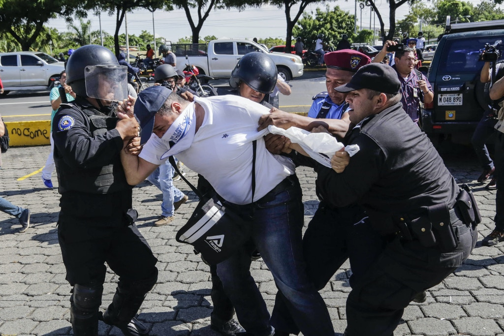TOPSHOT - A Nicaraguan man is arrested by riot police during a protest against the government of President Daniel Ortega in Managua, on October 14, 2018. (Photo by INTI OCON / AFP)        (Photo credit should read INTI OCON/AFP/Getty Images)