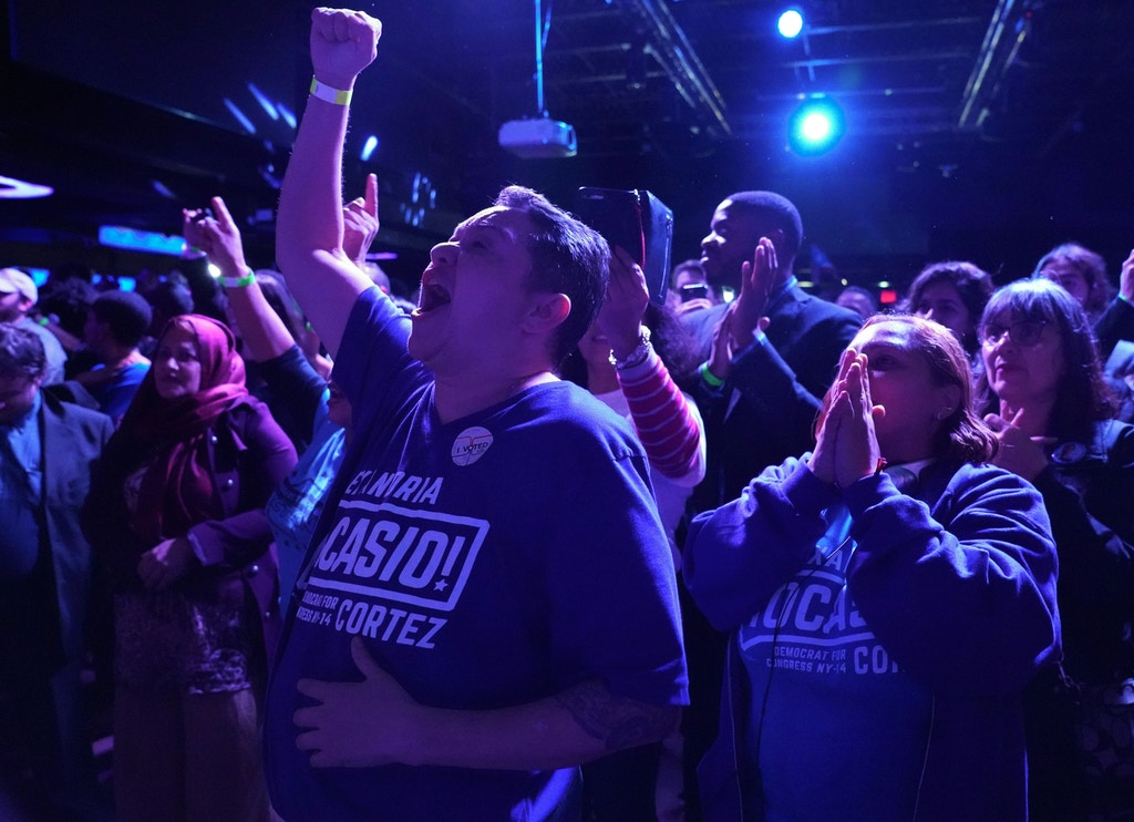 TOPSHOT - Supporters of Alexandria Ocasio-Cortez cheer while she speaks onstage during her election night party in the Queens Borough of New York on November 6, 2018. - 28-year-old Alexandria Ocasio-Cortez from New Yorks 14th Congressional district won Tuesdays election, defeating Republican Anthony Pappas and becomes the youngest woman elected to Congress. (Photo by Don EMMERT / AFP)        (Photo credit should read DON EMMERT/AFP/Getty Images)