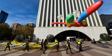 Amnesty International activists hold a giant dragonfly-shaped balloon with a banner reading