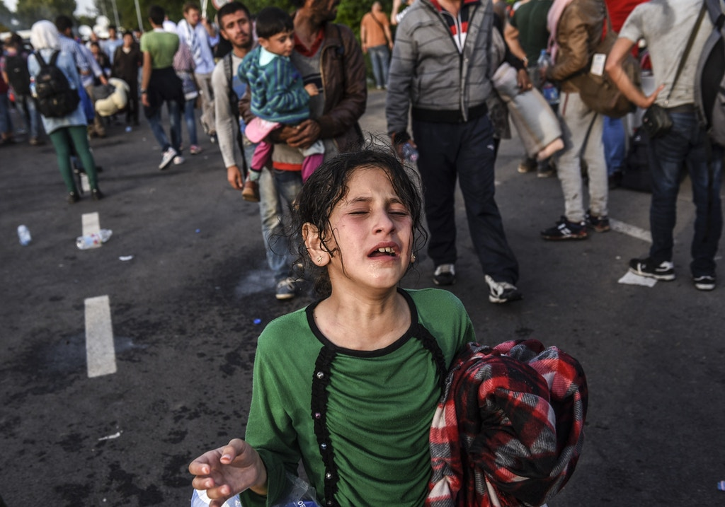 A girl reacts after receiving tear gas during clashes between migrants and Hungarian anti-riot police at the Hungarian border with Serbia near the town of Horgos on September 16, 2015. Europe's 20-year passport-free Schengen zone appeared to be a risk of crumbling with Germany boosting border controls on parts of its frontier with France as migrants desperate to find a way around Hungary's border fence began crossing into Croatia. With a string of EU countries tightened frontier controls in the face of the unprecedented human influx, the cherished principle of free movement across borders -- a pillar of the European project -- seemed in grave jeopardy. AFP PHOTO / ARMEND NIMANI        (Photo credit should read ARMEND NIMANI/AFP/Getty Images)