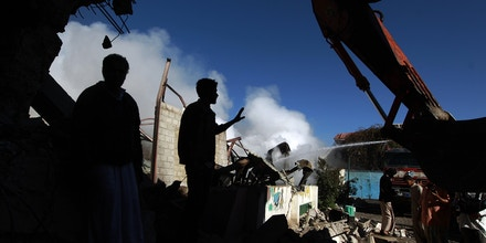 Yemenis stand amid the ruins of buildings destroyed in an air-strike by the Saudi-led coalition on February 10, 2016 in the capital Sanaa. The coalition has been carrying out air strikes against Iran-backed rebels across Yemen since March. / AFP / MOHAMMED HUWAIS (Photo credit should read MOHAMMED HUWAIS/AFP/Getty Images)