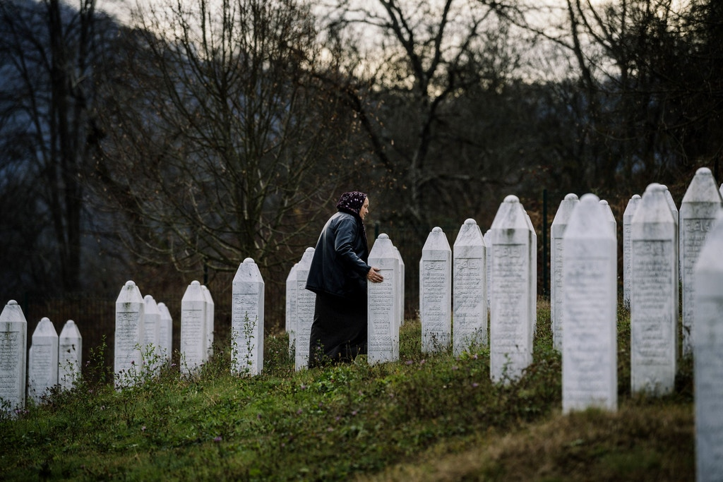 TOPSHOT - A Bosnian woman arrives to offer prayers beside gravestone at the memorial center of Potocari near Srebrenica on November 21, 2017.  On November 22, 2017, ICTY judges will deliver their verdict on Bosnian Serb wartime military chief Ratko Mladic, who faces 11 charges including genocide, war crimes and crimes against humanity -- arising from Bosnia's 1992-1995 war. / AFP PHOTO / Dimitar DILKOFF        (Photo credit should read DIMITAR DILKOFF/AFP/Getty Images)