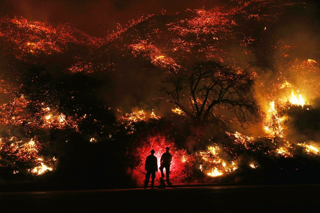 VENTURA, CA - DECEMBER 07:  Firefighters monitor a section of the Thomas Fire along the 101 freeway on December 7, 2017 north of Ventura, California. The firefighters occasionally used a flare device to burn-off brush close to the roadside. Strong Santa Ana winds are rapidly pushing multiple wildfires across the region, expanding across tens of thousands of acres and destroying hundreds of homes and structures.  (Photo by Mario Tama/Getty Images)