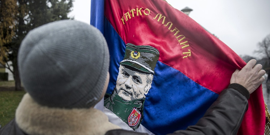 In this photograph taken on December 9, 2017, a Serbian nationalist holds a flag with an image of Bosnian Serb convicted war criminal Ratko Mladic, as he prepares to enter St. Sava Church in Belgrade, to attend prayers for the former Bosnian Serbian commander.Ratko Mladic, the wartime Bosnian Serb military chief, was given a life sentence on November 22, by the International Criminal Tribunal for the former Yugoslavia (ICTY) in The Hague, for genocide during the country's inter-ethnic war in the 1990s. / AFP PHOTO / OLIVER BUNIC (Photo credit should read OLIVER BUNIC/AFP/Getty Images)