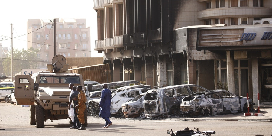 Security forces stand in front of the burned exterior of the Splendid Hotel after an Al Qaeda attack that killed 30 people there and in a restaurant across the street in Ouagadougou, Burkina Faso, January 16, 2016. Joe Penney