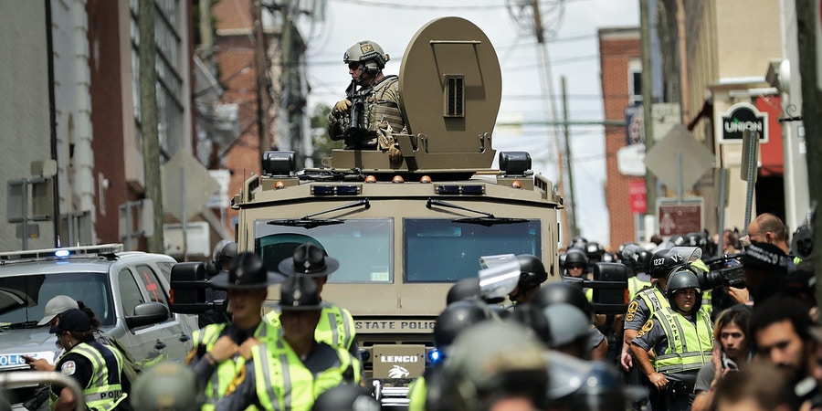 CHARLOTTESVILLE, VA - AUGUST 12:  A Virginia State Police officer in riot gear keeps watch from the top of an armored vehicle after car plowed through a crowd of counter-demonstrators marching through the downtown shopping district August 12, 2017 in Charlottesville, Virginia. The care plowed through the crowed following the shutdown of the Unite the Right rally by police after white nationalists, neo-Nazis and members of the