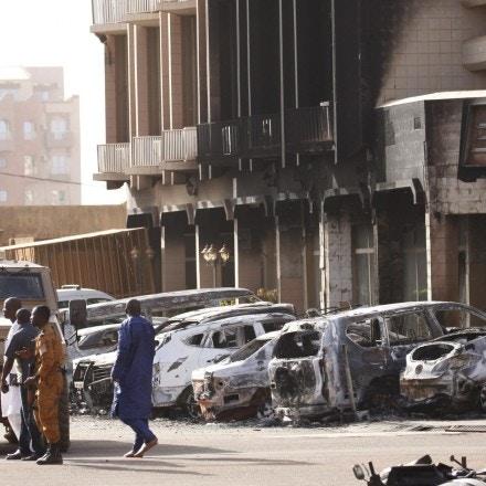 As forças de segurança ficam em frente ao exterior queimado do Splendid Hotel em Ouagadougou, Burkina Faso, em 16 de janeiro de 2016, um dia depois de um ataque da Al Qaeda ter matado 30 pessoas em um restaurante do outro lado da rua.