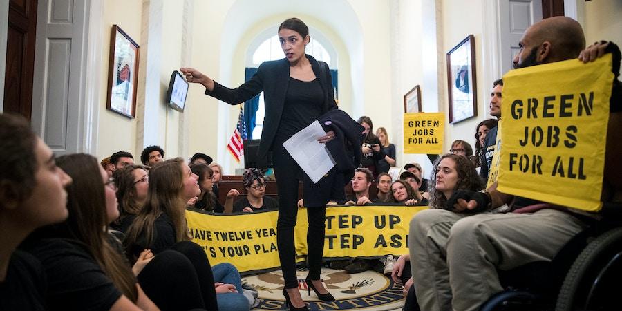 Alexandria Ocasio-Cortez fala com ativistas do movimento Sunrise Movement que protestam nos escritórios da líder da minoria da Câmara, Nancy Pelosi, em Washington D.C., em 13 de novembro.
