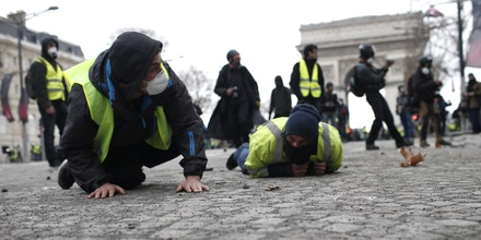 Demonstrators drop flat to the ground on the Champs-Elysees avenue during a protest Saturday, Dec. 8, 2018 in Paris. Crowds of yellow-vested protesters angry at President Emmanuel Macron and France's high taxes tried to converge on the presidential palace Saturday, some scuffling with police firing tear gas, amid exceptional security measures aimed at preventing a repeat of last week's rioting. (AP Photo/Rafael Yaghobzadeh)