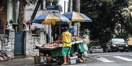 Ambulante com barraca de frutas no bairro de Perdizes, zona oeste de São Paulo.