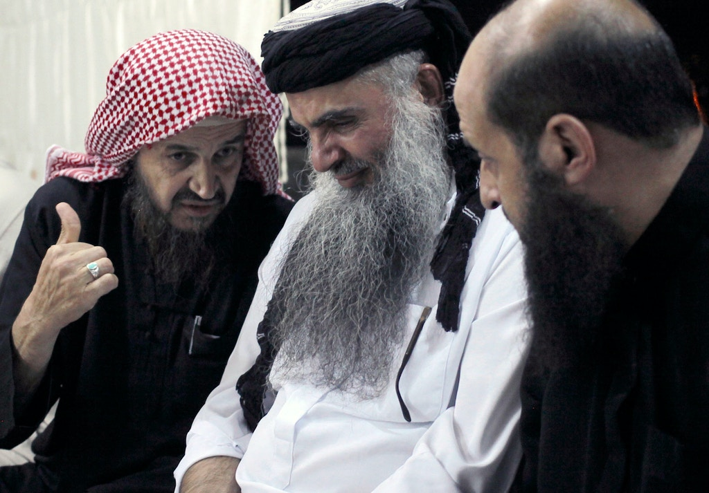 In this Wednesday, Sept. 24, 2014 photo, radical al-Qaida-linked preacher Abu Qatada, second right, listens to the renowned jihadi ideologue, Abu Mohammed al-Maqdisi, left, on the day Abu Qatada was released from Jordanian prison after an acquittal on security charges, in Amman, Jordan. Abu Qatada and al-Maqdisi, held court on the rooftop of a villa whispering to each other and rising occasionally from plastic chairs to greet supporters. The two have denounced some of the Islamic State group's practices as un-Islamic - comments some analysts say have turned the preachers into assets in Jordan's campaign to contain the Islamic State, which is believed to have attracted thousands of followers in Jordan. (AP photo/Mohammad Hannon)